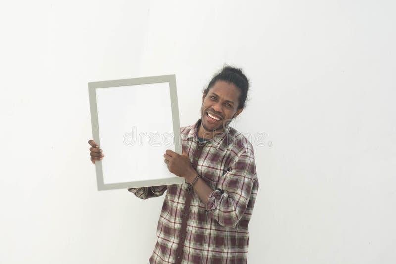 Ένας νέος μαύρος που κρατά το λευκό πίνακα με το απομονωμένο υπόβαθρο στο λευκό στοκ εικόνα
