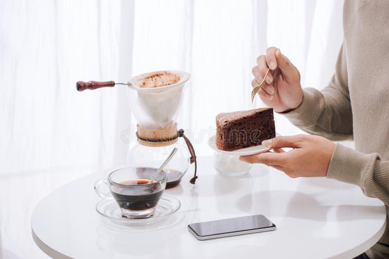 Ένας νεαρός άνδρας κάθεται στον καφέ κατανάλωσης καφετεριών και κατανάλωση του κέικ Με το διάστημα αντιγράφων στοκ εικόνα με δικαίωμα ελεύθερης χρήσης