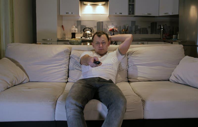 Ένας νεαρός άνδρας που κάθεται στο σπίτι σε έναν καναπέ το βράδυ με τον τηλεχειρισμό στο χέρι του, που εξετάζει άμεσα τη κάμερα στοκ εικόνες