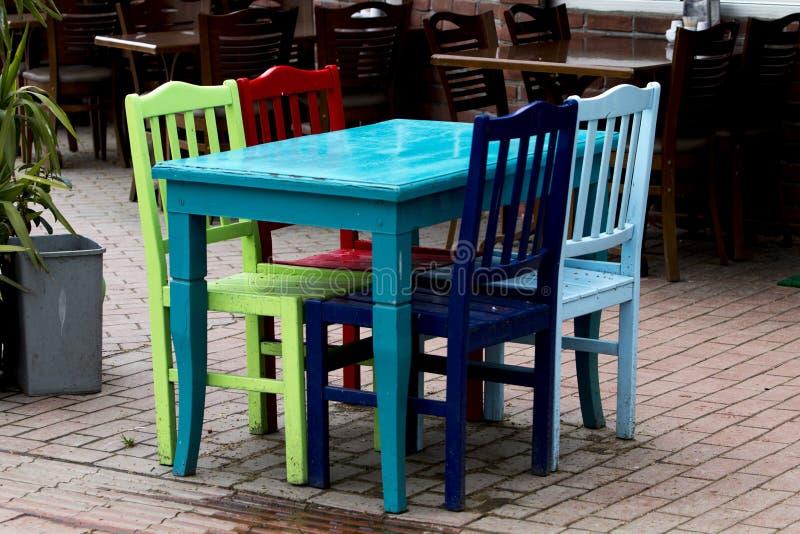 Ένας τυρκουάζ πίνακας, και πράσινες, κόκκινες, μπλε και σκούρο μπλε καρέκλες ενός εστιατορίου στο sideway στοκ εικόνα με δικαίωμα ελεύθερης χρήσης