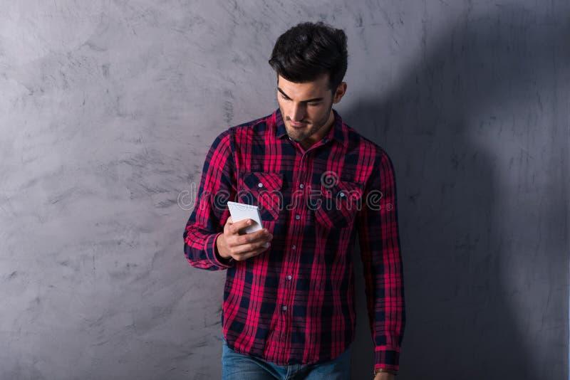 Ένας χαμογελώντας νεαρός άνδρας που χρησιμοποιεί το smartphone του σε ένα κόκκινο πουκάμισο στοκ εικόνα με δικαίωμα ελεύθερης χρήσης