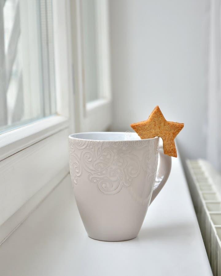 Ένα άσπρο φλυτζάνι του τσαγιού ή ένα φλιτζάνι του καφέ με ένα μπισκότο με μορφή ενός αστεριού από το παράθυρο στοκ εικόνα