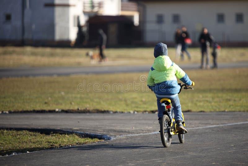 Ένα αγόρι στον ιματισμό Demi-εποχής οδηγά ένα ποδήλατο σε έναν δρόμο ασφάλτου Η νεώτερη γενεά συμμετέχει στον αθλητισμό και ξοδεύ στοκ εικόνα με δικαίωμα ελεύθερης χρήσης