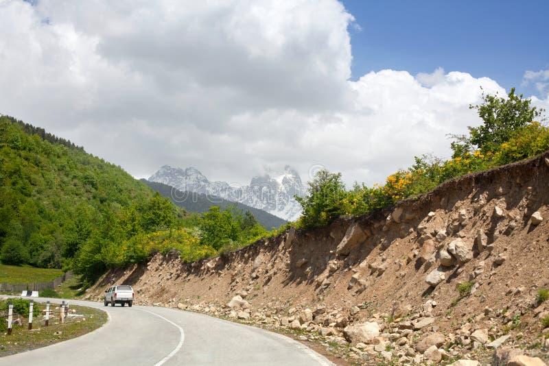 Ένα αυτοκίνητο σε έναν ελικοειδή δρόμο στα βουνά, αιχμές βουνών στο χιόνι και το πράσινο υπόβαθρο λόφων στοκ φωτογραφία