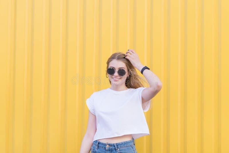 Ένα ευτυχές κορίτσι θέτει στη κάμερα ενάντια στο σκηνικό ενός φωτεινού κίτρινου τοίχου και χαμογελά στοκ φωτογραφία