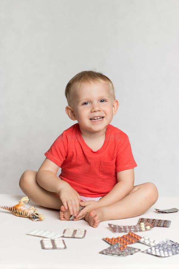 Ένα ευτυχές μικρό παιδί μωρών σε μια ζωντανή μπλούζα χρώματος κοραλλιών κάθεται μεταξύ των χαπιών και των φαρμάκων στοκ φωτογραφίες