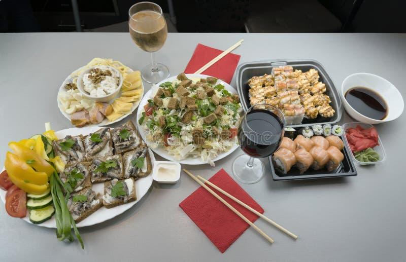 Ένα θαυμάσιο ρομαντικό γεύμα για δύο με τους ιαπωνικούς ρόλους και τα ποτήρια του κόκκινου κρασιού και του άσπρου κρασιού στοκ φωτογραφία με δικαίωμα ελεύθερης χρήσης