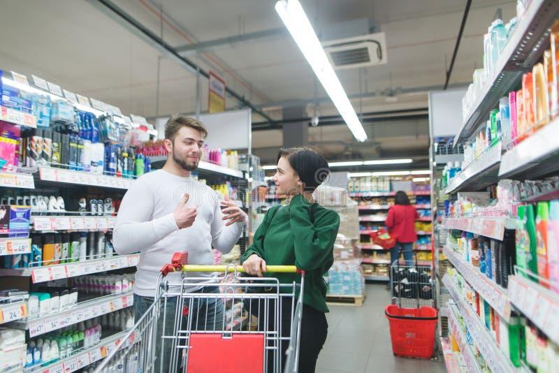 Ένα θετικό ζευγάρι είναι στο οικιακό τμήμα της υπεραγοράς και επικοινωνεί Οικογένεια που ψωνίζει σε μια υπεραγορά στοκ εικόνες