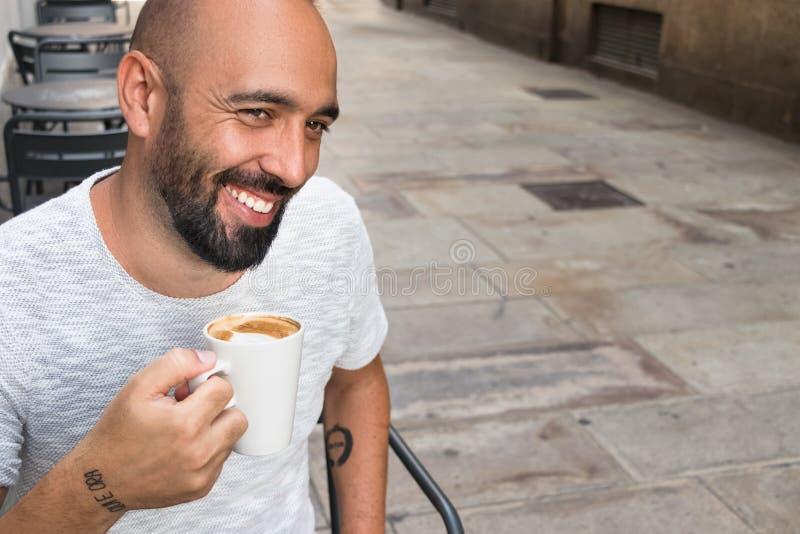 Ένα ισπανικό άτομο που χαμογελά έχοντας τον καφέ υπαίθρια στοκ εικόνες