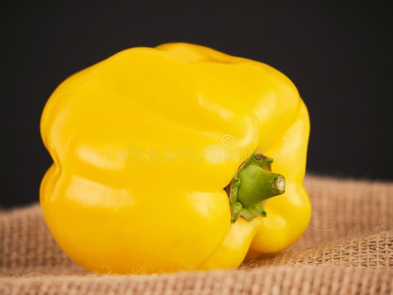 Ένα κίτρινο πιπέρι με ένα αγροτικό υπόβαθρο στοκ φωτογραφίες
