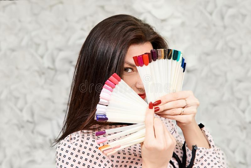 Ένα κορίτσι με ένα όμορφο μανικιούρ, που κρατά τα δείγματα μανικιούρ, που καλύπτουν το πρόσωπό της brunette στοκ εικόνα