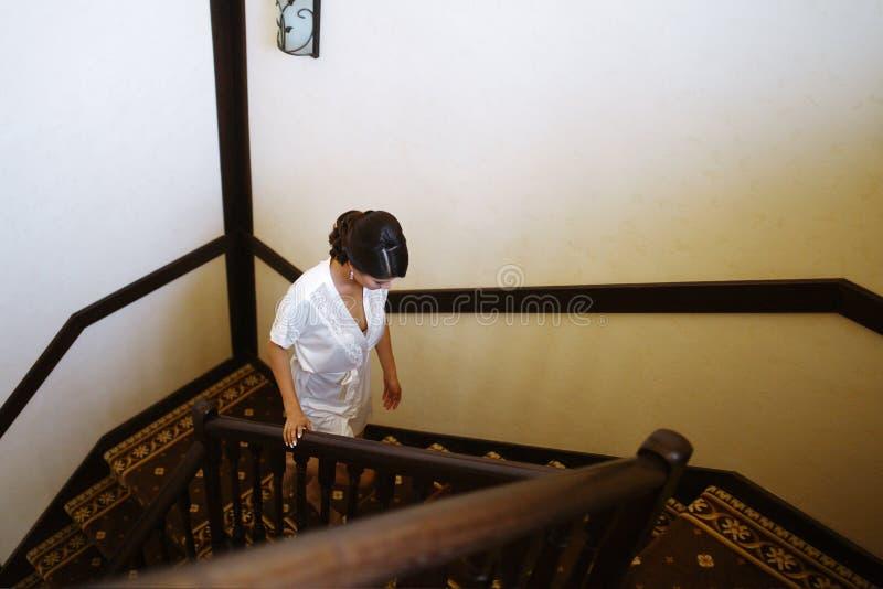 Ένα κορίτσι σε μια άσπρη τήβεννο αναρριχείται στα σκαλοπάτια και κοιτάζει κάτω από τα πόδια της στοκ φωτογραφία με δικαίωμα ελεύθερης χρήσης