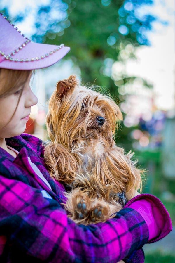 Ένα κορίτσι στα ζωηρόχρωμα ενδύματα κρατά μια μικρή φυλή σκυλιών του τεριέ του Γιορκσάιρ Τα παιδιά αγαπούν animals_ στοκ εικόνες με δικαίωμα ελεύθερης χρήσης