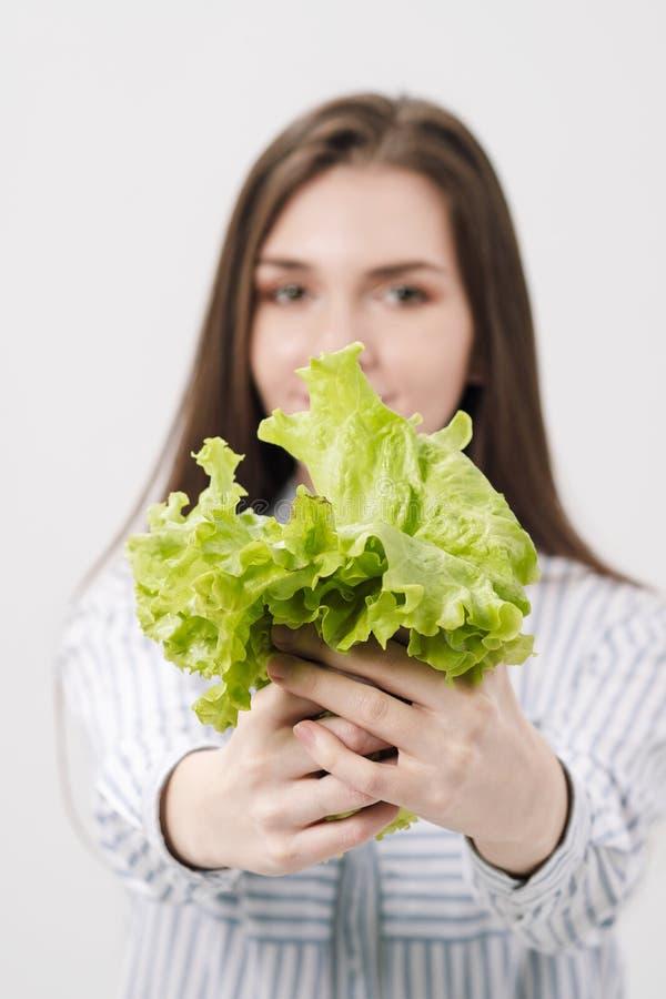 Ένα λεπτό κορίτσι brunette με μακρυμάλλη σε ένα άσπρο υπόβαθρο, κρατά στα χέρια της και παρουσιάζει τα φύλλα πράσινου φρέσκου στοκ εικόνα