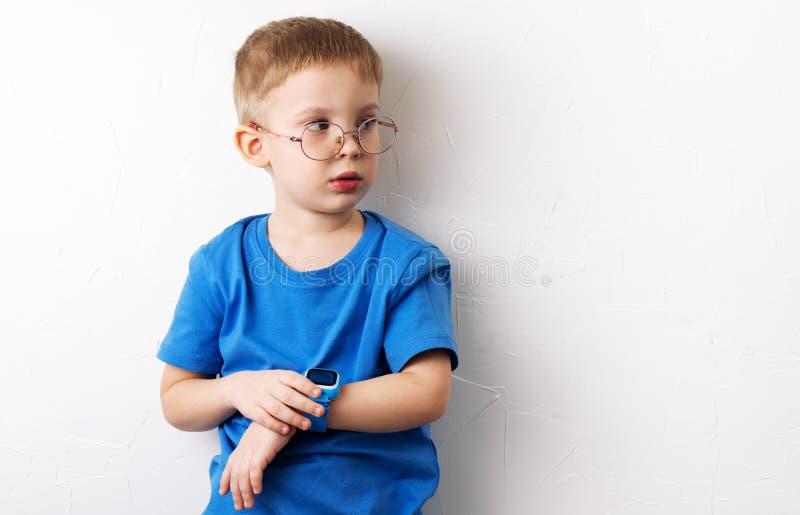 Ένα μικρό αγόρι στα γυαλιά και σε μια μπλε μπλούζα με ένα μπλε έξυπνο ρολόι σε ετοιμότητα του βρίσκεται στο πάτωμα σε ένα λευκό στοκ εικόνες