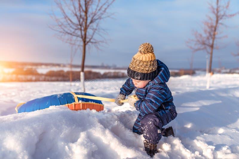 Ένα μικρό αγόρι, 2-3 χρονών, χειμερινό παιχνίδι συρσίματος, που τραβά από χιονισμένο snowdrift από το χειμώνα πάρκων λόφων Έννοια στοκ φωτογραφίες