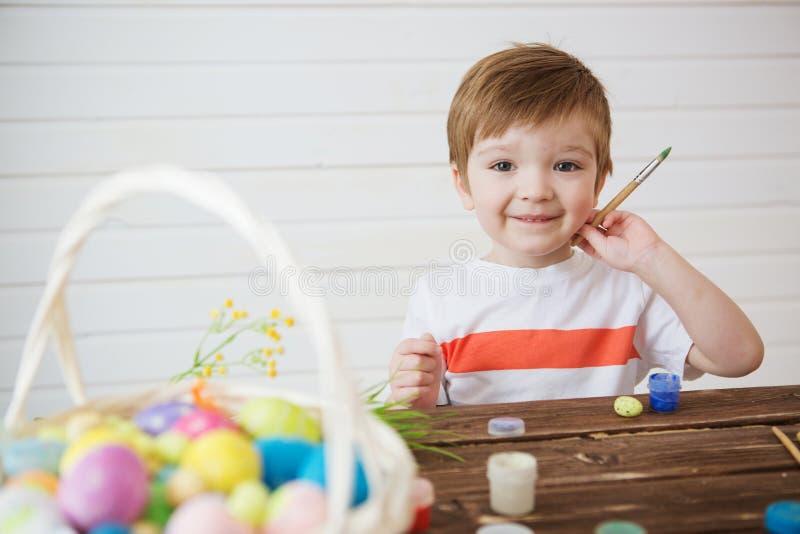 Ένα μικρό αγόρι που χρωματίζει και που διακοσμεί τα αυγά Πάσχας Πορτρέτο του χαριτωμένου αγοριού 3 χρονών Κρατά τη βούρτσα και χρ στοκ εικόνες
