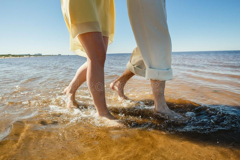 Ένα νέο ζεύγος έχει τη διασκέδαση και περπατά στο θαλάσσιο νερό Τα πόδια κλείνουν επάνω Ρομαντική ημερομηνία στην παραλία στοκ φωτογραφίες