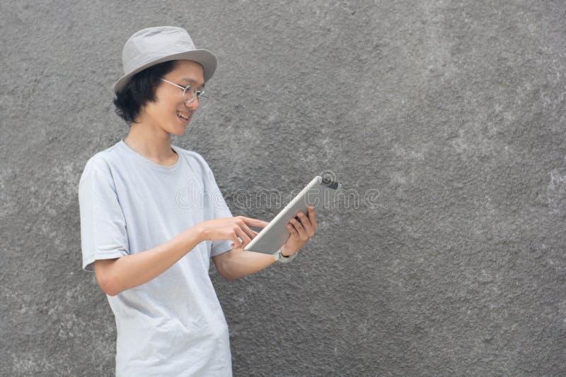 Ένα νέο atractive δημιουργικό ασιατικό άτομο με το καπέλο fedora και γυαλιά που δείχνουν στον υπολογιστή και το χαμόγελο ταμπλετώ στοκ εικόνες