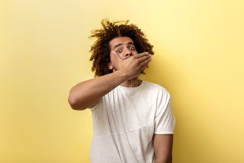 Ένα σγουρό διευθυνμένο μαυρισμένο άτομο κρατά το χέρι του στο στόμα του Μυστικοπαθής και έκπληκτη προοπτική στοκ φωτογραφίες