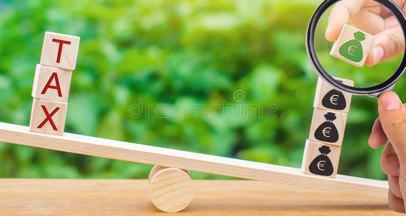 Ένα χέρι βάζει τους ξύλινους φραγμούς με το ευρώ στις κλίμακες και το φόρο λέξης Έννοια της επιτυχούς φορολογικής πληρωμής Επιστρ στοκ εικόνα
