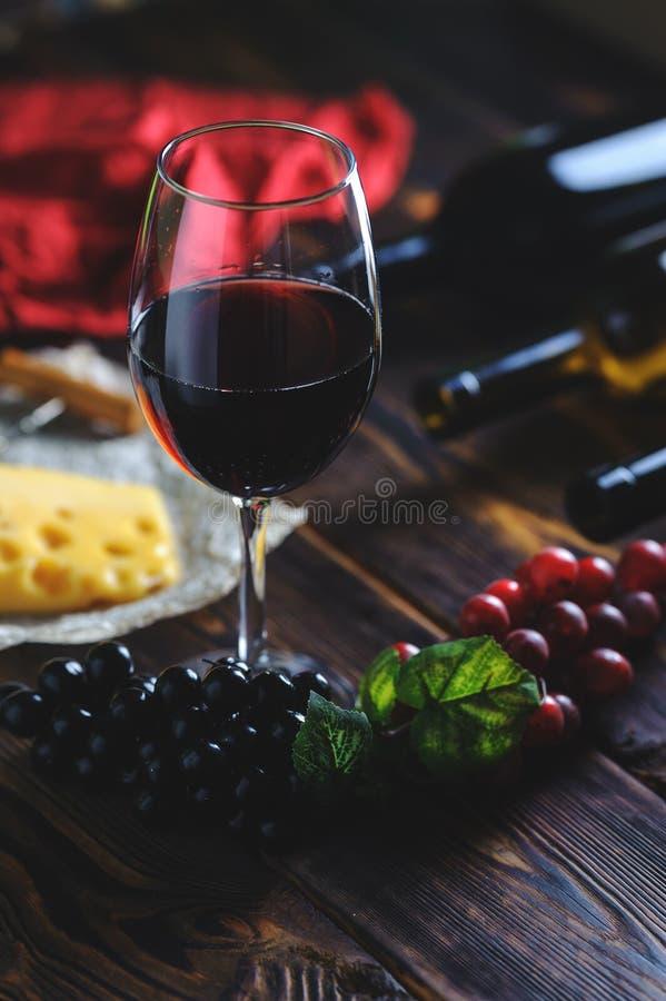 Ένα ποτήρι του κόκκινου κρασιού με την κινηματογράφηση σε πρώτο πλάνο σταφυλιών στοκ εικόνες με δικαίωμα ελεύθερης χρήσης