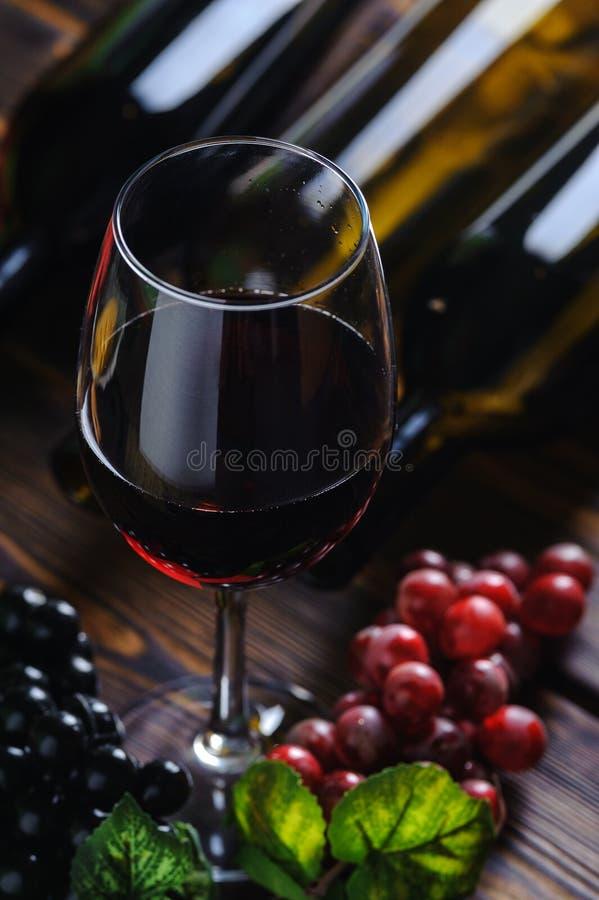 Ένα ποτήρι του κόκκινου κρασιού με την κινηματογράφηση σε πρώτο πλάνο σταφυλιών στοκ φωτογραφίες