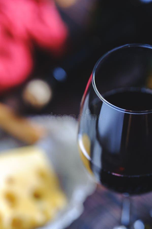 Ένα ποτήρι του κόκκινου κρασιού με την κινηματογράφηση σε πρώτο πλάνο σταφυλιών στοκ φωτογραφία με δικαίωμα ελεύθερης χρήσης