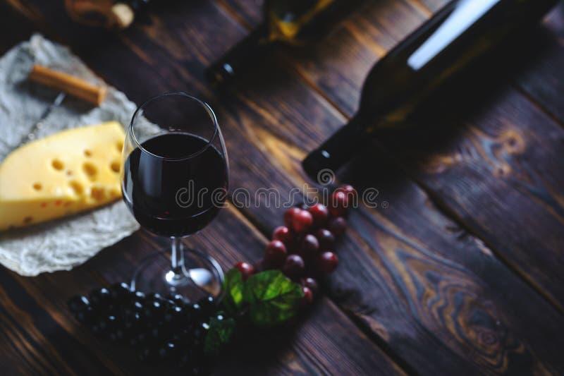 Ένα ποτήρι του τυριού και των σταφυλιών κόκκινου κρασιού στοκ φωτογραφία