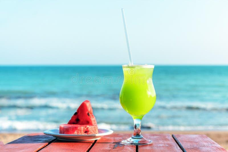 Ένα ποτήρι του φρέσκου πράσινου τροπικού χυμού φρούτων στην παραλία, και ένα πιάτο με το καρπούζι στον πίνακα, ενάντια στη θάλασσ στοκ εικόνα