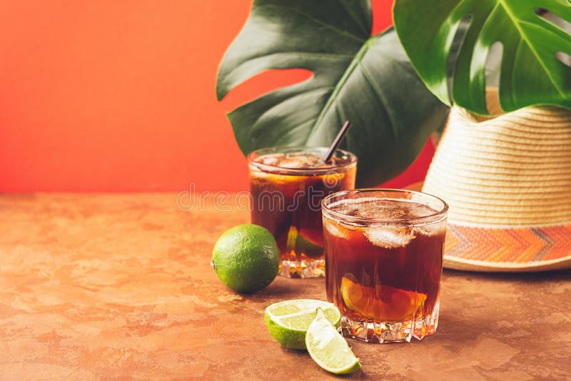 Ένα ποτό των κύβων πάγου ρουμιού ή κόλας και juicy ασβέστης goblets γυαλιού σε ένα κλίμα των τροπικών πράσινων φύλλων στοκ εικόνα με δικαίωμα ελεύθερης χρήσης