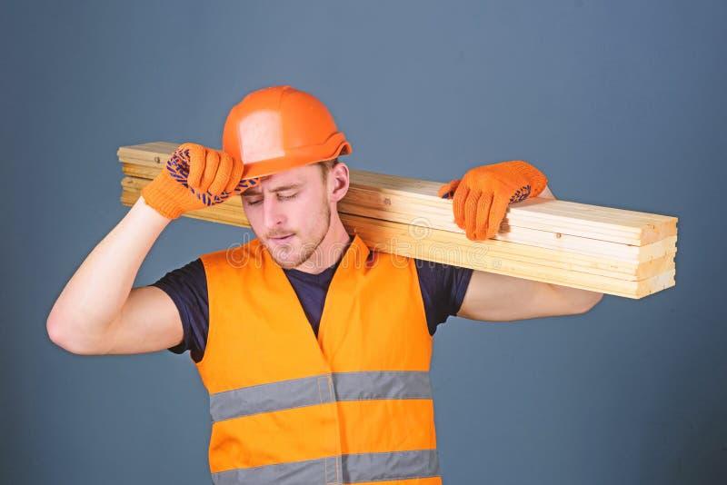 Έννοια ασφάλειας και προστασίας Ο ξυλουργός, woodworker, ισχυρός οικοδόμος στο πολυάσχολο πρόσωπο φέρνει την ξύλινη ακτίνα στον ώ στοκ φωτογραφίες