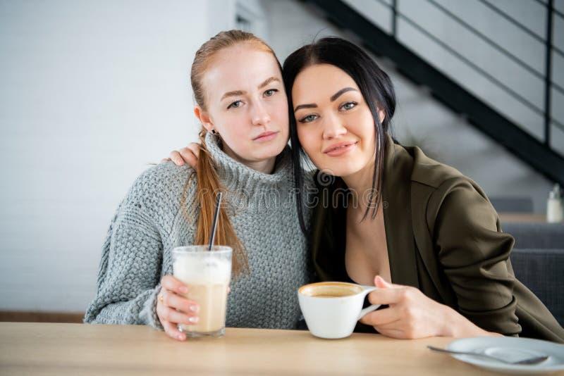Έννοια επικοινωνίας και φιλίας - χαμογελώντας νέες γυναίκες με τα φλυτζάνια καφέ στον καφέ στοκ εικόνα
