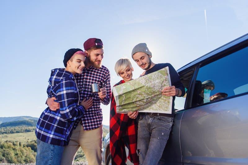 Έννοια θερινού ταξιδιού Ευτυχείς φίλοι που χρησιμοποιούν νοικιασμένη χαρτών εγγράφου πλησίον το αυτοκίνητο στη φύση Ευτυχείς ταξι στοκ φωτογραφία με δικαίωμα ελεύθερης χρήσης