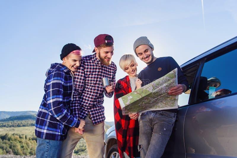 Έννοια θερινού ταξιδιού Ευτυχείς φίλοι που χρησιμοποιούν νοικιασμένη χαρτών πλησίον το αυτοκίνητο στη φύση Ευτυχείς ταξιδιώτες hi στοκ εικόνα με δικαίωμα ελεύθερης χρήσης