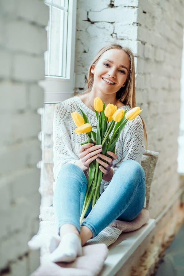Έννοια ομορφιάς και τρυφερότητας Πορτρέτο της όμορφης γυναίκας με την ανθοδέσμη των κίτρινων τουλιπών που κάθονται στη στρωματοει στοκ φωτογραφία με δικαίωμα ελεύθερης χρήσης