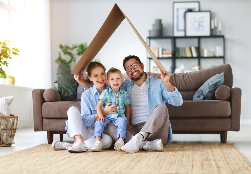 Έννοια της κατοικίας και του επανεντοπισμού ευτυχείς πατέρας οικογενειακών μητέρων και γιος παιδιών με τη στέγη στο σπίτι στοκ εικόνα με δικαίωμα ελεύθερης χρήσης