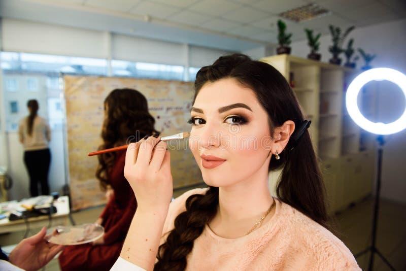 Έννοια Visage Κλείστε επάνω να πάρει γυναικών αποτελεί στα βλέφαρα Εφαρμογή της σκιάς ματιών με τη βούρτσα από τον επαγγελματία κ στοκ φωτογραφία