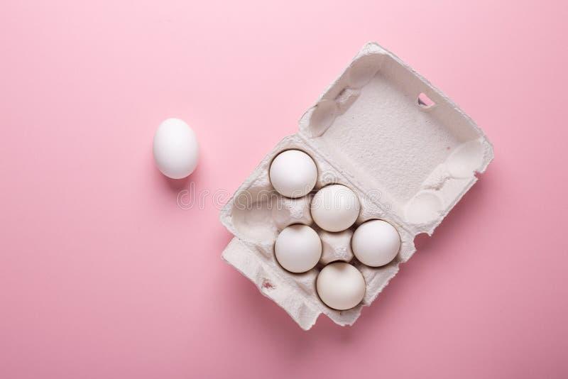 Έξι άσπρα αυγά στο κιβώτιο χαρτοκιβωτίων στο ρόδινο εγγράφου υποβάθρου επίπεδο Πάσχας τοπ συμβόλων άποψης ευτυχές βρέθηκαν στοκ φωτογραφία με δικαίωμα ελεύθερης χρήσης