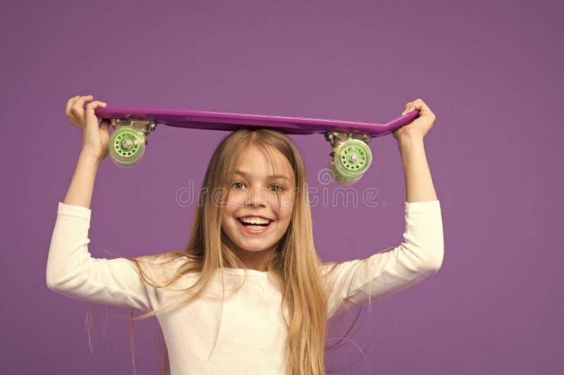 έτοιμος γύρος Να κάνει σκέιτ μπορντ είναι διασκέδαση Ευτυχές κορίτσι σκέιτερ στο ιώδες υπόβαθρο Ανάπτυξη και ευτυχία παιδικής ηλι στοκ φωτογραφίες με δικαίωμα ελεύθερης χρήσης