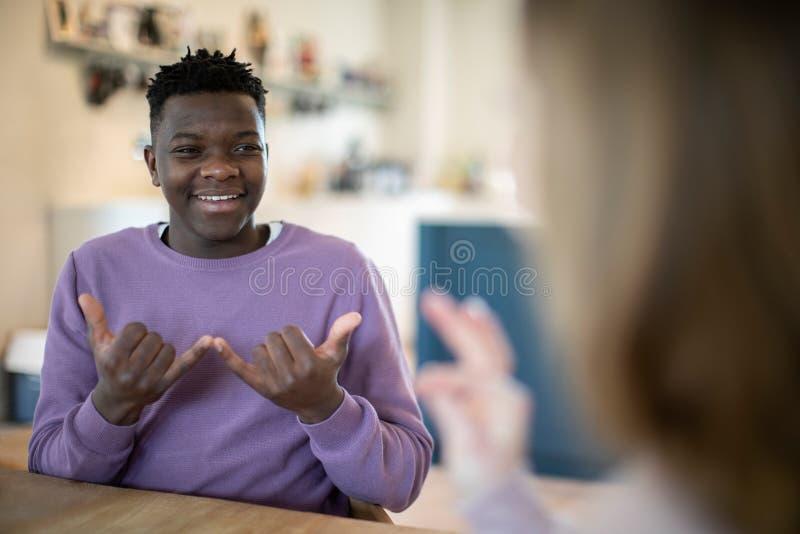 Έφηβος και κορίτσι που έχουν τη συνομιλία που χρησιμοποιεί τη γλώσσα σημαδιών στοκ φωτογραφία