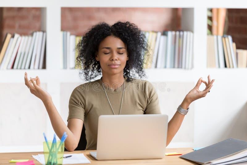 Ήρεμη μαύρη επιχειρηματίας που παίρνει το σπάσιμο που κάνοντας τη γιόγκα στην εργασία στοκ εικόνες