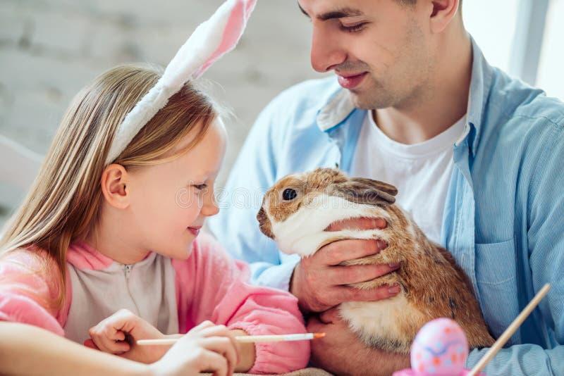 Αγαπάμε τις όμορφες παραδόσεις Τα αυγά χρωμάτων Mom και κορών, μπαμπάς κρατούν ένα εγχώριο διακοσμητικό κουνέλι στοκ εικόνες με δικαίωμα ελεύθερης χρήσης