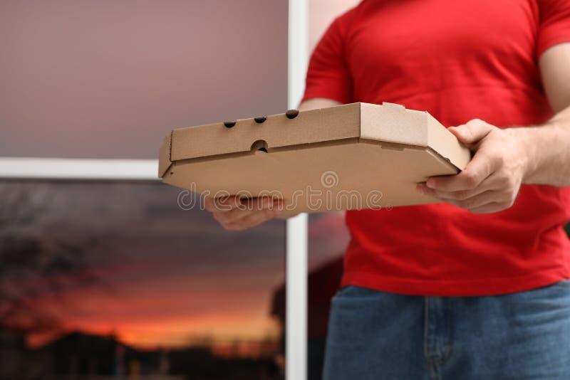 Αγγελιαφόρος με το κιβώτιο πιτσών στο θολωμένο υπόβαθρο στοκ εικόνες με δικαίωμα ελεύθερης χρήσης
