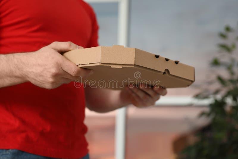 Αγγελιαφόρος με το κιβώτιο πιτσών στο θολωμένο υπόβαθρο στοκ φωτογραφίες