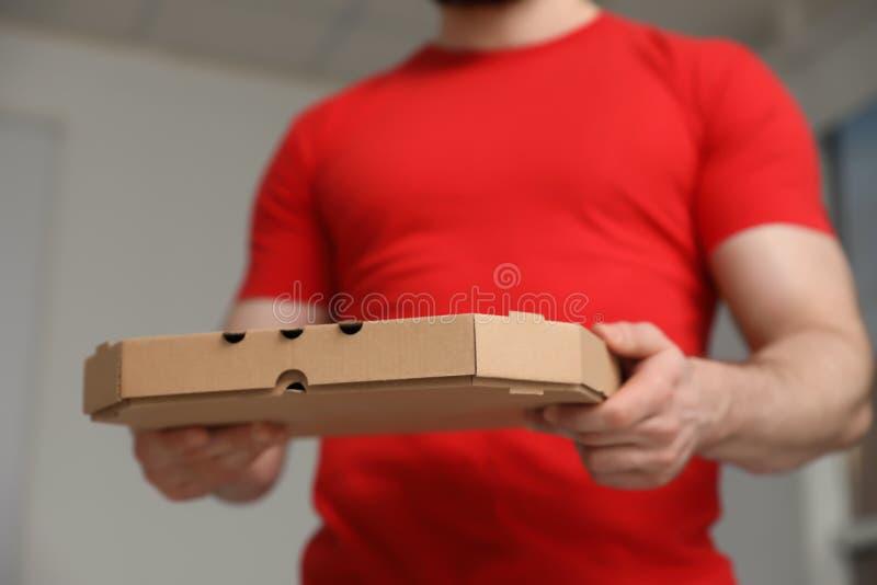 Αγγελιαφόρος με το κιβώτιο πιτσών στο θολωμένο υπόβαθρο στοκ φωτογραφία με δικαίωμα ελεύθερης χρήσης