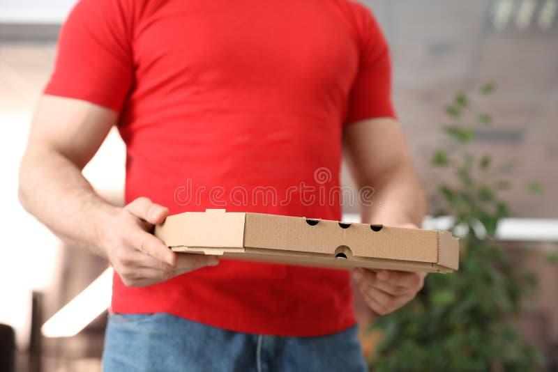 Αγγελιαφόρος με το κιβώτιο πιτσών στο θολωμένο υπόβαθρο στοκ φωτογραφίες με δικαίωμα ελεύθερης χρήσης