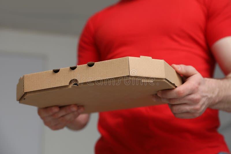 Αγγελιαφόρος με το κιβώτιο πιτσών στο θολωμένο υπόβαθρο στοκ φωτογραφία