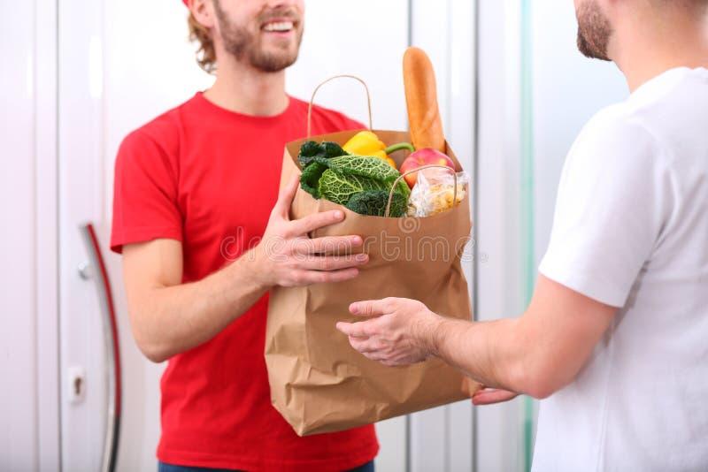 Αγγελιαφόρος που δίνει την τσάντα εγγράφου με τα προϊόντα στον πελάτη στο σπίτι, κινηματογράφηση σε πρώτο πλάνο Παράδοση τροφίμων στοκ εικόνα με δικαίωμα ελεύθερης χρήσης