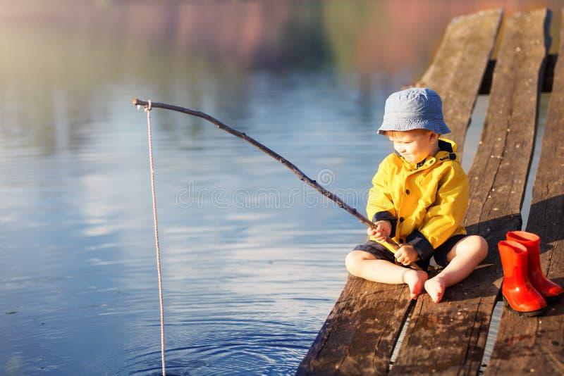 Αγόρι στην ξύλινη αποβάθρα με ένα δίχτυ του ψαρέματος στοκ εικόνες